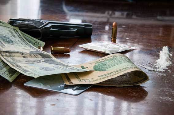 money, drugs, and gun on a table