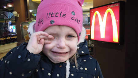 Girl crying outside a McDonald's restaurant