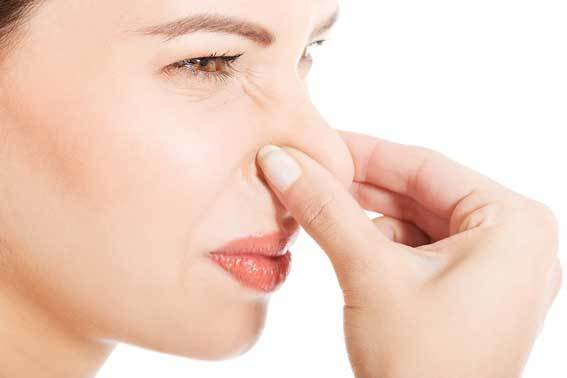 woman pinching nose to avoid bad smell
