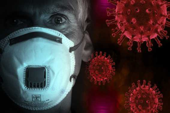 A scared older man wearing a face mask to protect himself from a virus