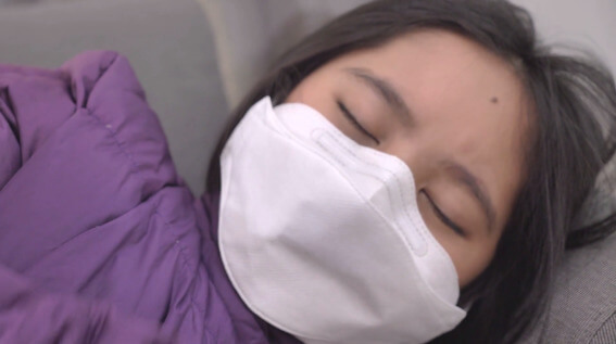 Sick Chinese girl wearing a mask