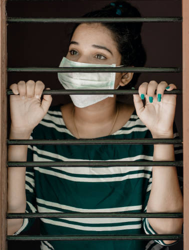Woman wearing mask behind bars
