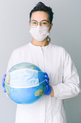 Masked woman holding a world globe with a mask around it