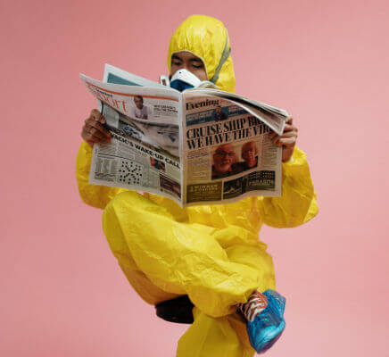 Man in hazmat suit reading a newspaper