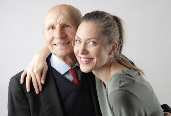 Young woman hugging an old man