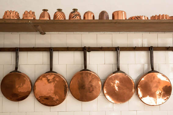 Copper cookware hanging on the wall