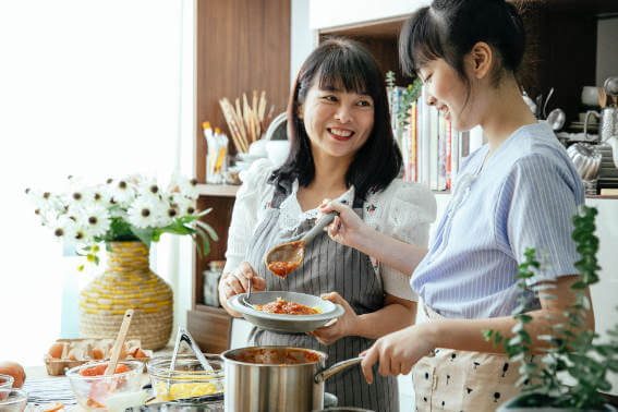 Mother and daughter cooking in stainless steel pots