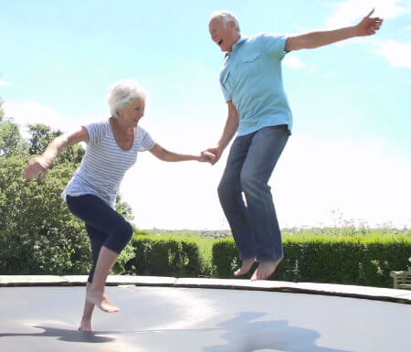 Old couple jumping on a trampoline