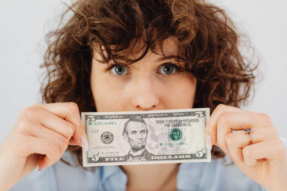 Woman covering her mouth with a dollar bill