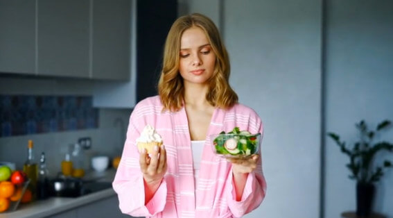 Woman choosing betweeen salad or cake to eat a low sodium diet